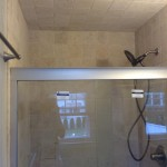New shower tile and glass shower doors installed.