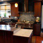 Custom kitchen island, cabinets, tile backsplash, and appliances.