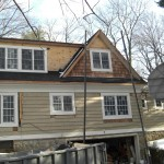New cedar shake siding is being installed on the house. New windows have also been installed.