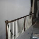 The hallway and railing at the top of the curved staircase.