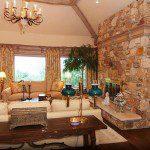 Custom millwork on ceiling, stone fireplace, and Pella windows.