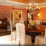 Formal dining room with mural on walls.