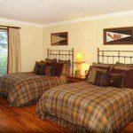 Bedroom featuring Pella windows and wood flooring.