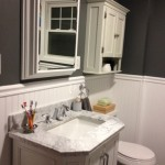 The bathroom completed - new vanity, mirror, and storage installed on the wall.