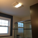 A view of the ceiling showing the new bathroom exhaust fan/light combo and the glass shower doors in Hasbrouck Heights, NJ.
