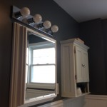 The bathroom in Hasbrouck Heights is completed - new vanity light, mirror, and storage unit installed on the wall.