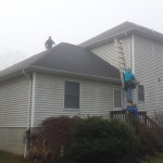 Preparing to remove the old shingles at the rear of the house.