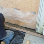 After removing the rotted door saddle, concrete is added to build up the new door threshold in Spotswood, NJ.