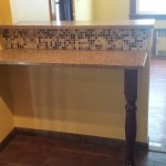 A view of the new counter area with backsplash between the dining room and kitchen. The custom leg holds up the one side of the granite countertop.
