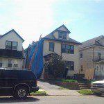 Roof demolition begins on the left side of the house in Elizabeth, NJ.
