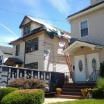 The right side of the house in Elizabeth, NJ has had its old shingles removed and new plywood installed.