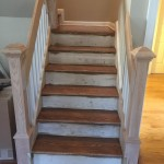 The staircase after staining the treads and installation of wood floor landing.