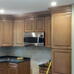 Almost completed kitchen in Chatham, NJ with new wood cabinets, backsplash, new microwave, recessed lighting, and granite countertops.